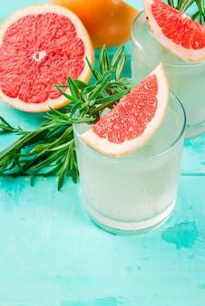 Alkoholgetränk, rosemary, pampelmuse u. gin cocktail, auf hellblauer holztischoberfläche
