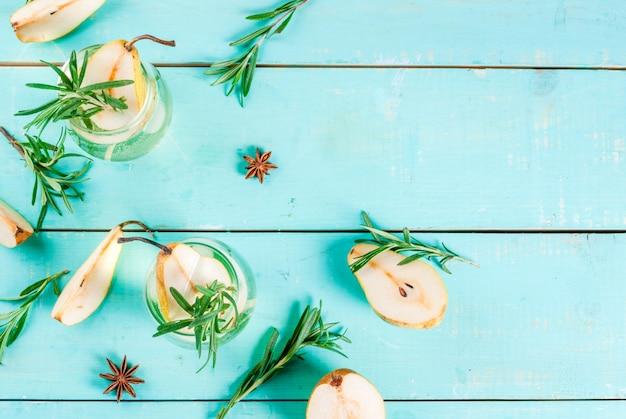 Alkoholgetränk, süßes birnencocktail mit rum, alkohol, anis und rosmarin, auf hellblauem holztisch, draufsicht