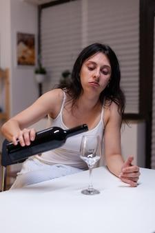 Alkoholische frau, die eine flasche wein und ein glas hat und sich zu hause traurig fühlt. einsame person, die ein getränk mit alkohol trinkt, das depressiv ist. erwachsene mit sucht fühlen sich emotional und verärgert