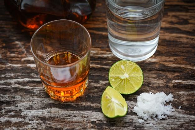 Alkoholische getränke und hölzerner hintergrundweinbrand des zitronensalzes in einem glas mit alkoholflaschen und -wasser