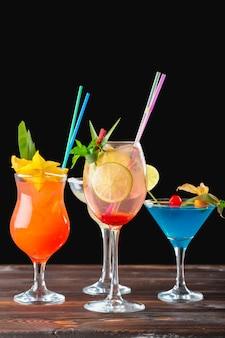 Alkoholische und alkoholfreie cocktails auf holztisch, kalte getränke des sommers