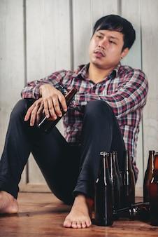 Alkoholischer asiatischer mann, der allein trinkendes bier sitzt