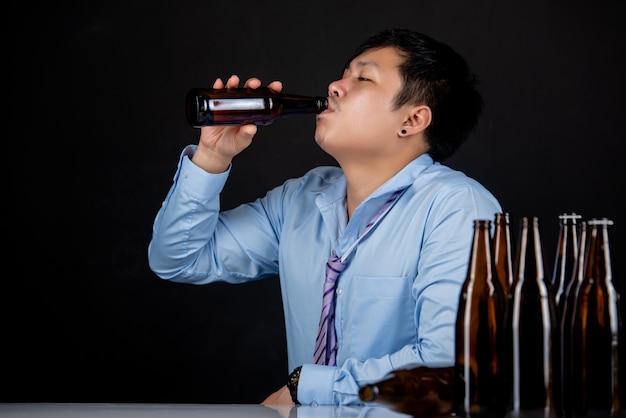 Alkoholischer asiatischer mann mit vielen bierflaschen