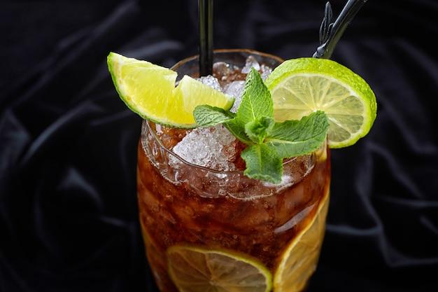 Alkoholischer cocktail, long island eistee, auf schwarzem samt, auf schwarzem hintergrund