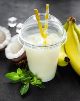 Alkoholischer frischer cocktail von pina colada, kalt serviert mit kokosnuss und banane auf einer schwarzen oberfläche