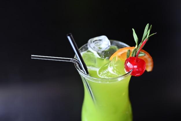 Alkoholischer grüner cocktail mit likören auf schwarzem hintergrund