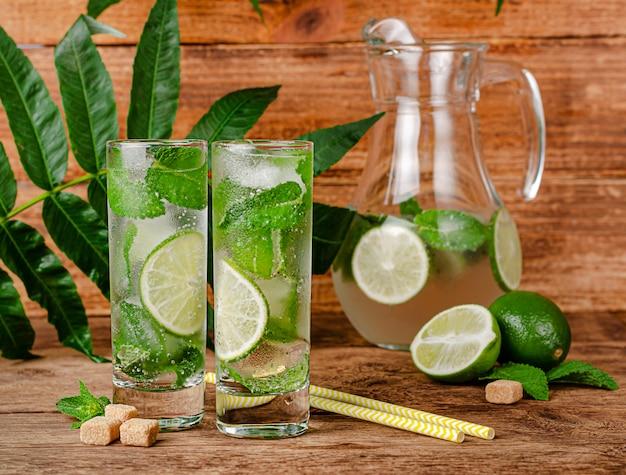 Alkoholischer mojito-cocktail mit limette, rohrzucker, minze und eis auf holztisch. sommergetränkekonzept