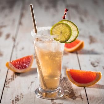 Alkoholischer salziger hundecocktail mit grapefruit und limette im glas auf holz