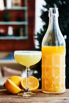 Alkoholisches cocktail limoncello sauer diente in einem glasweinglas und in einer flasche auf holztisch