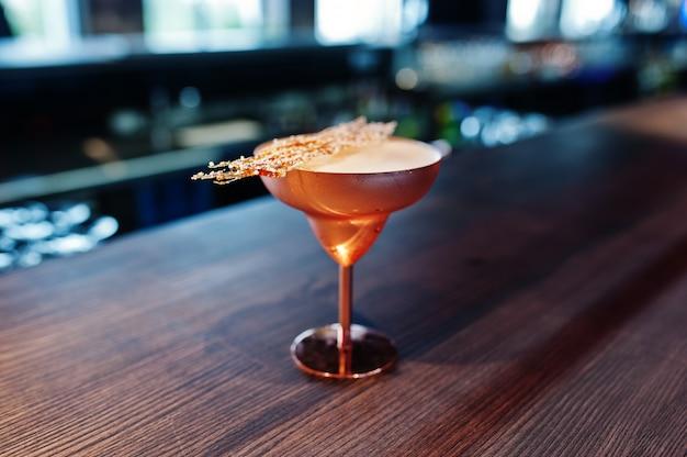 Alkoholisches cocktail mit puderzucker im bronzeglas auf bartisch