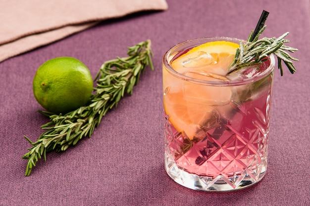 Alkoholisches getränk an der bar mit limette und rosmarin