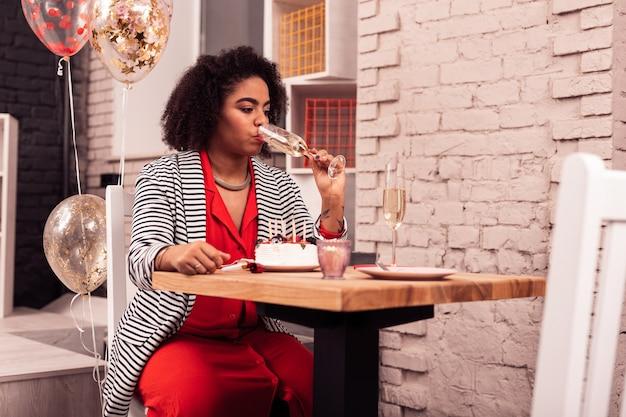 Alkoholisches getränk. angenehme afroamerikanische frau, die einen schluck champagner nimmt, während sie ihren geburtstag allein feiert