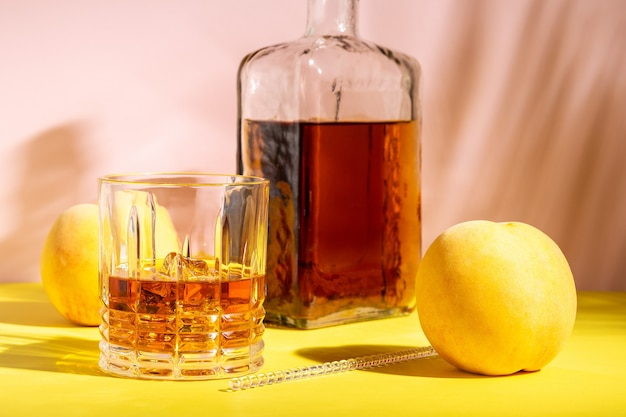 Alkoholisches getränk in einem glas mit einem pfirsich an einer hellen wand.