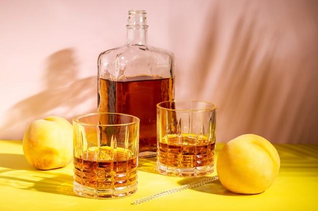 Alkoholisches getränk in einem glas mit einem pfirsich