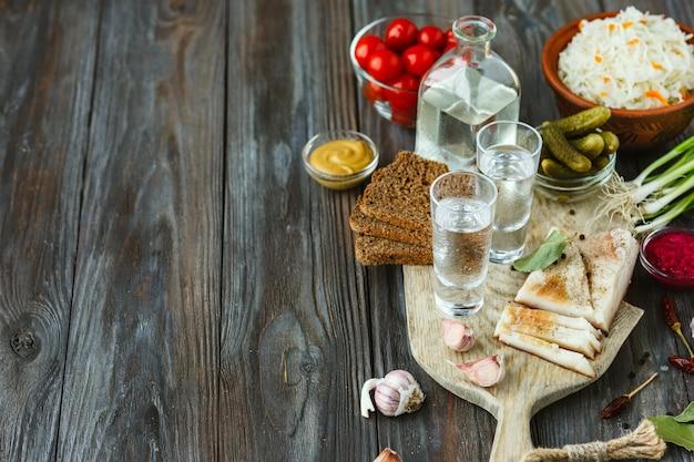 Alkoholisches getränk mit schmalz, gesalzenem gemüse auf hölzernem hintergrund. alkohol purer craft drink und traditioneller snack, tomaten, kohl, gurken. negativer raum. feiern und lecker.