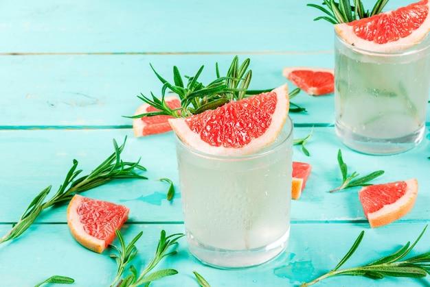 Alkoholisches getränk, rosmarin, grapefruit & gin cocktail, auf hellblauem holztisch,