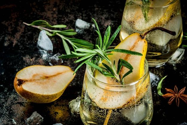 Alkoholisches getränk, süßer birnencocktail mit rum, alkohol, anis und rosmarin, auf einem schwarzen rostigen metallic,
