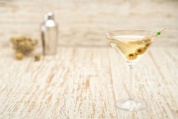 Alkoholisches getränkecocktail mit grünen oliven auf holztisch