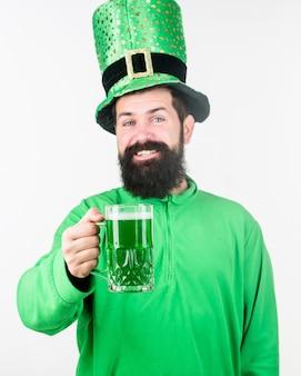 Alkoholkonsum integraler bestandteil des st. patricks day. irische tradition. mann brutaler bärtiger hipster trinken pint bier. irischer pub. bier trinken teil feier. saisonale feiertagskarte der bar. grüner bierkrug.