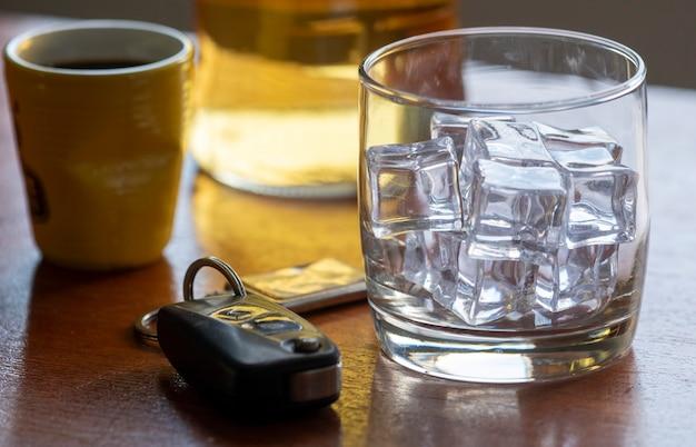 Alkoholmissbrauch mit glas whisky mit eis und autoschlüssel auf dem tisch.