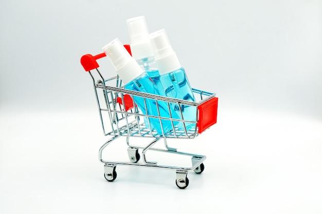 Alkoholspray in einer kleinen plastikflasche auf dem einkaufswagen
