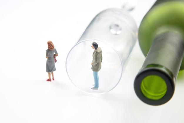 Alkoholsüchtiger miniaturmann vor dem hintergrund einer flasche wein