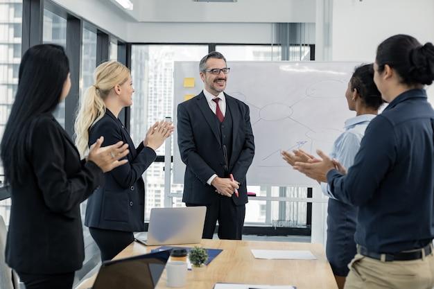 Alle am besprechungsstand lächelten und applaudierten dem leiter des teams, das erfolgreich mit glücklich zusammenarbeitete. geschäftskonzept für gruppentreffen.