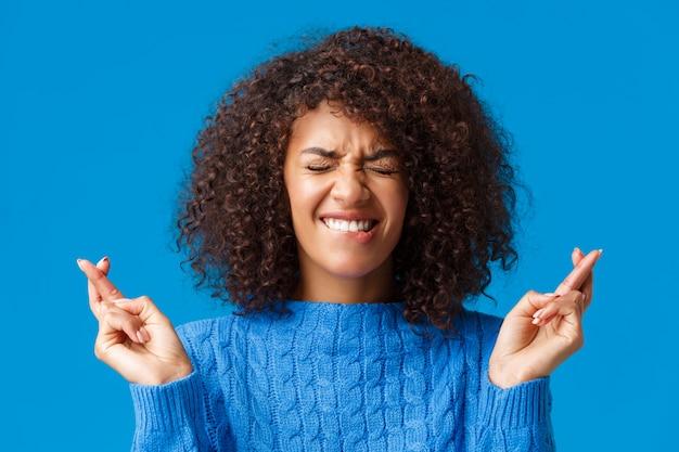 Alle anstrengungen im gebet um wünsche werden wahr. hoffnungsvoller netter afroamerikanerfrauen-wunschtraum erfüllen, nahe augen und lächelnder eifriger gewinn, daumen viel glück und beten, blau