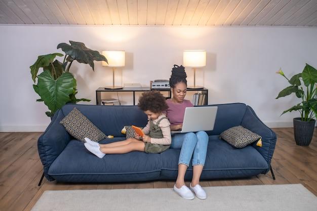 Alle beschäftigt. kleines interessiertes dunkelhäutiges mädchen mit tablet und junge fokussierte mutter mit laptop, die auf dem sofa in einem schönen gemütlichen zimmer sitzt