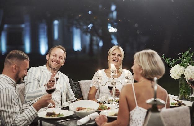 Alle lachen jetzt. erfolgreicher witz. eine gruppe erwachsener freunde ruht sich abends im hinterhof des restaurants aus und unterhält sich.