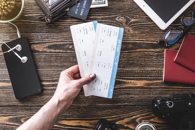 Alle notwendigen dinge für den flug im urlaub. flugtickets, reisepass, telefon und kreditkarte auf einem hölzernen hintergrund