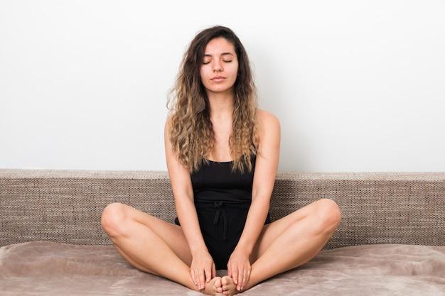 Alle schlechte energie aus nachrichten befreien. junge frau mit lockigen haaren im lotus posiert beim meditieren und yoga zu hause