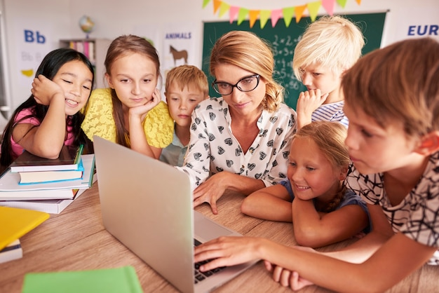 Alle schüler um einen laptop