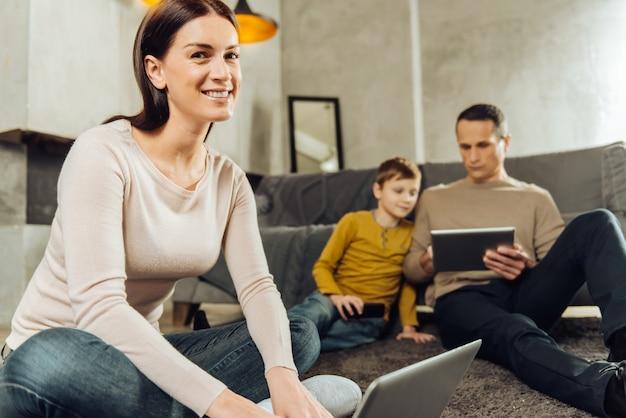 Alle sind beschäftigt. der fokus liegt auf einer fröhlichen jungen frau, die an einem laptop arbeitet und in die kamera lächelt, während ihr mann und ihr sohn im hintergrund videos auf tablets ansehen