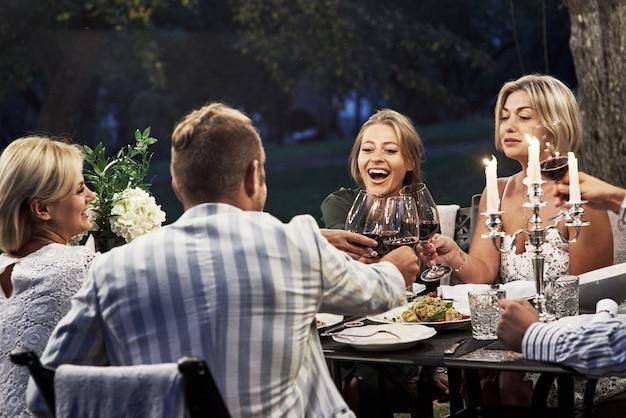 Alle sind glücklich. eine gruppe erwachsener freunde ruht sich abends im hinterhof des restaurants aus und unterhält sich.