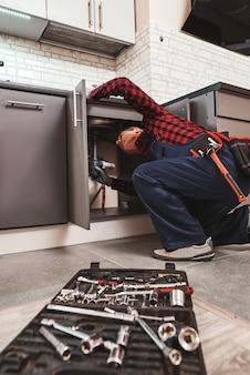Alle werkzeuge für alle fälle senior handwerker repariert waschbecken in der küche