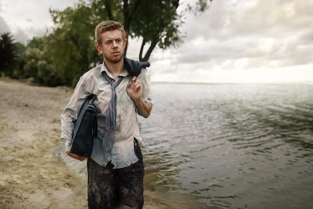 Allein geschäftsmann im zerrissenen anzug, der auf dem strand auf einsamer insel geht. geschäftsrisiko, zusammenbruch oder insolvenzkonzept