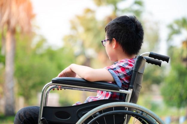 Allein junger behinderter mann auf rollstuhl im park