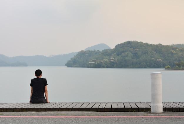 Allein junger mann, der auf dem hölzernen gehweg schaut zum berg im see mit sonnenuntergang sitzt