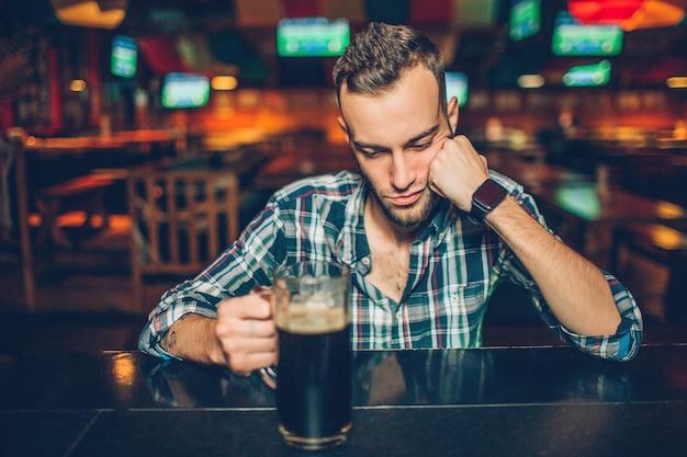Allein junger mann sitzen am bartresen in der kneipe. er schläft. griffhand des jungen mannes auf becher mit dunklem bier.