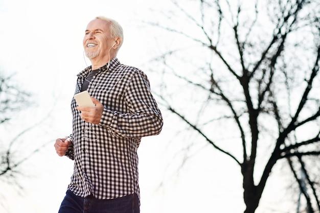 Allein mit der natur. niedriger winkel des energetischen älteren mannes, der musik hört und natur genießt