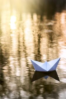 Allein papierboot segeln entlang des flusses bei sonnenuntergang