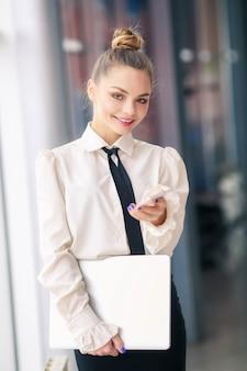 Allein wooman. geschäftsporträt in einer weißen bluse und einem schwarzen rock macht einträge in einem notizbuch vor dem hintergrund des bürozentrums.