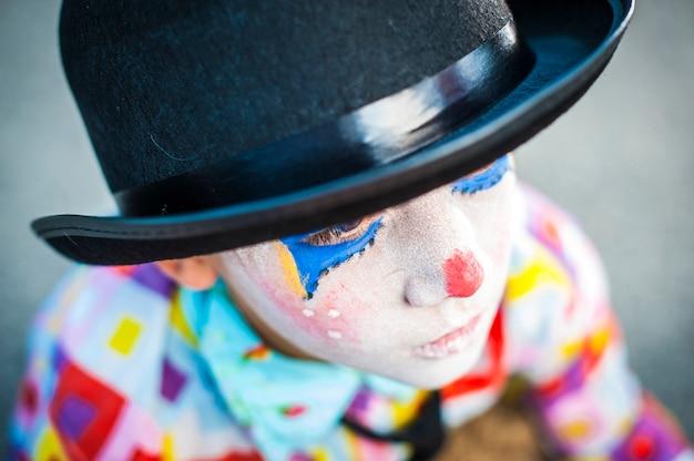 Alleiner junge 8/6 jahre alt mit clown make-up - traurig mit hut