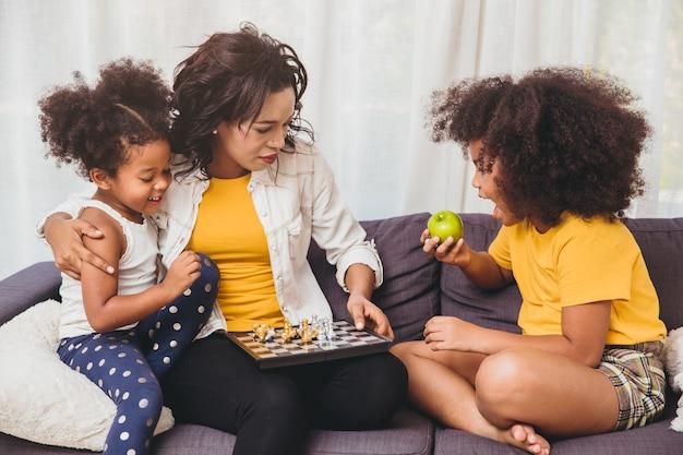 Alleinerziehende mutter gute pflege, bringt ihren kindern bei, genie zu sein, und kluge kleine mädchen, die lernen, schachbrettspiel zu spielen und obst für die gesundheit zu essen.