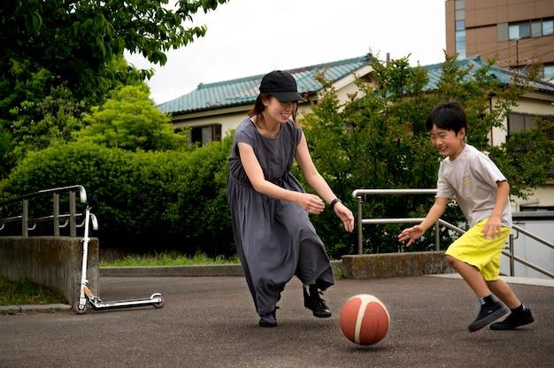 Alleinerziehende mutter spielt basketball mit ihrem sohn