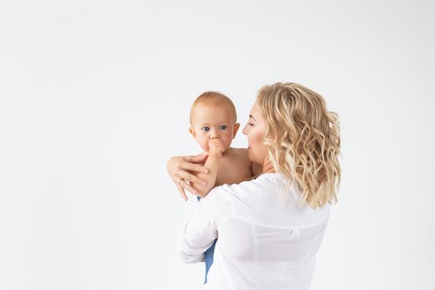Alleinerziehendes, mutterschafts- und babyzeitkonzept - mutter, die süßes baby auf weißer wand hält