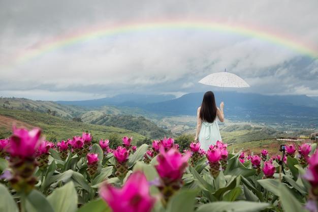 Alleinfrau, die regenschirm mit schönem regenbogen im blumengarten, hintere ansicht hält.