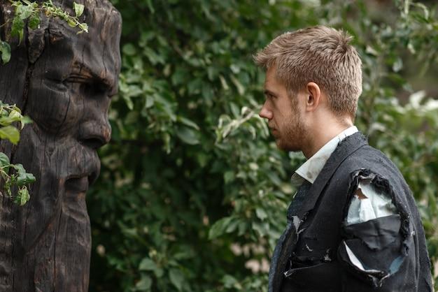 Alleiniger geschäftsmann im zerrissenen anzug, der an der hölzernen statue auf verlorener insel steht.