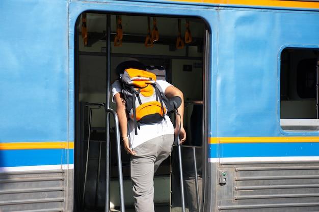 Alleinreisende steigen mit rucksack in den zug